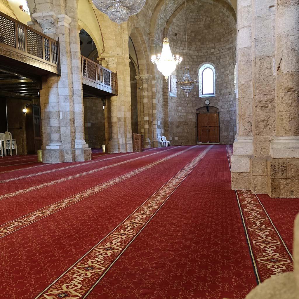 Ein Beirut Reisetipp, der nach der Hitze und dem Trubel der Straßen gut tut: Der große Gebetsaal der al-ʿUmarī-Moschee, von Pfeilern aus hellem Sandstein getragen, ist kühl temperiert und mit einem prächtigen roten Teppich ausgelegt.]
