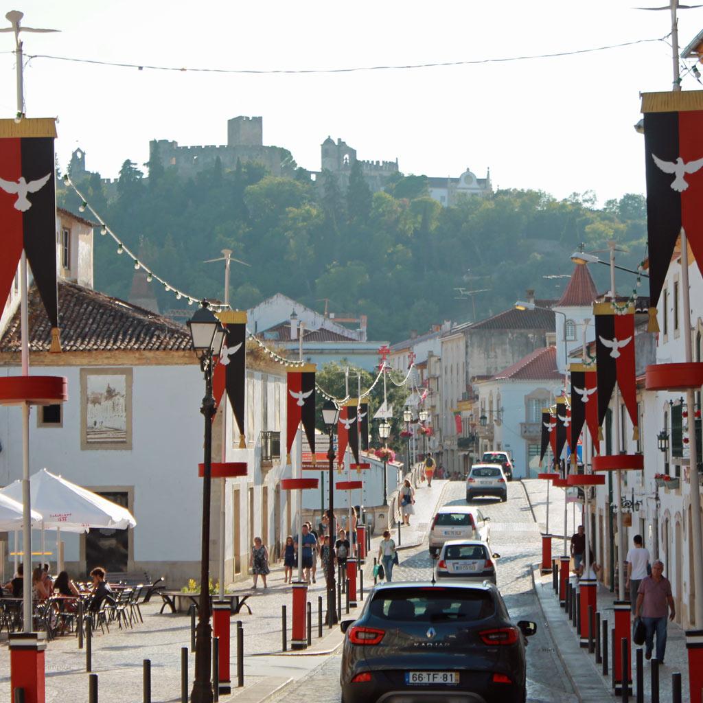 Eine mit Wimpeln geschmückte Straße in Tomar im Herzen Portugals. Im Hintergrund thront auf einem Hügel das burgähnliche Kloster der Tempelritter.