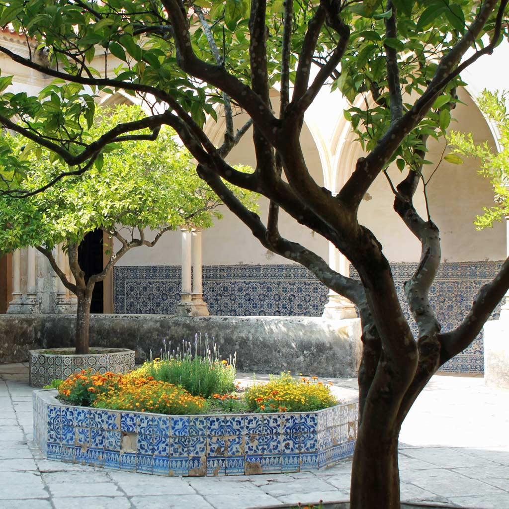 Innenhof eines Kreuzgangs mit Bäumen und einem zum Beet umfunktionierten Brunnen. Die Spitzbogenarkaden werden von Doppelsäulen getragen, die Wände zieren Azulejos mit blauen Ziermotiven.
