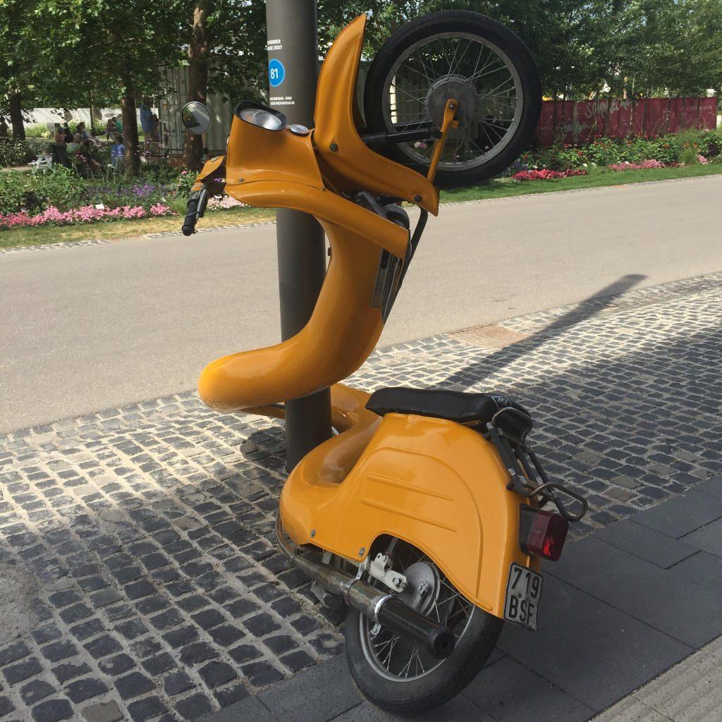 Skulptur eines kanariengelben Motorrollers, der sich wie eine Schlange um einen Laternenpfahl windet. Skulpturen sind ein wichtiger Bestandteil der diesjährigen Bundesgartenschau.