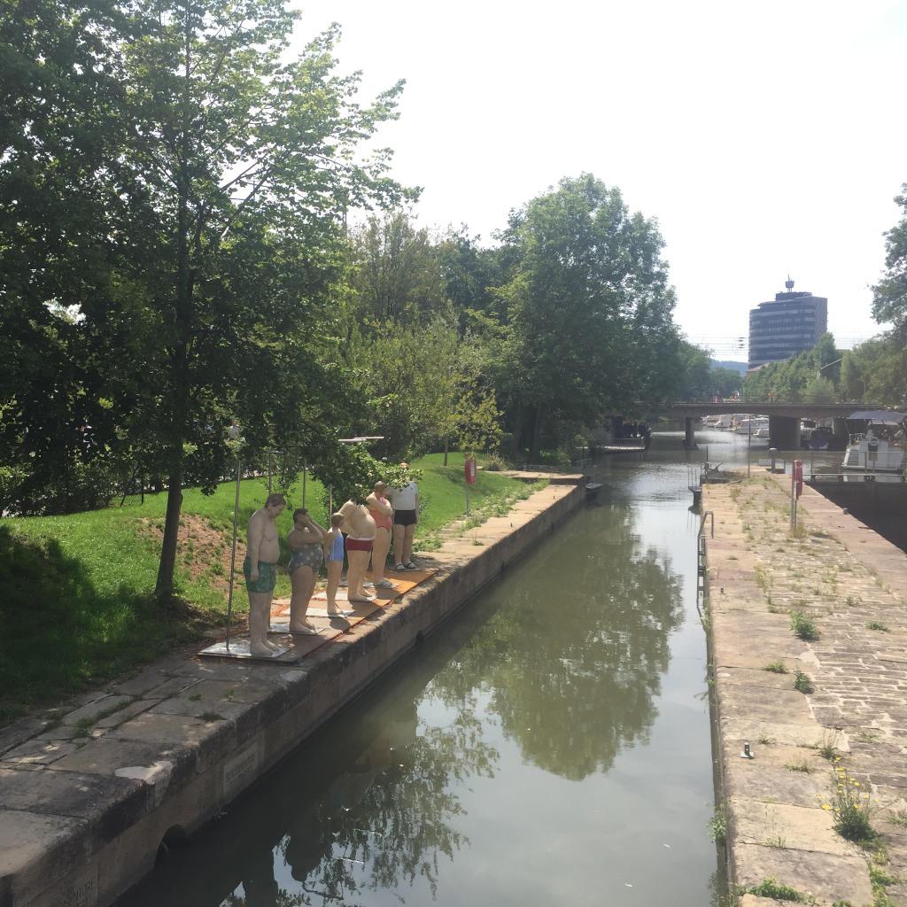 Fünf Skulpturen, die Badende darstellen, stehen am Rande einer historischen Schleuse, die zum Gelände der Bundesgartenschau gehört. Das Wasser ist spiegelglatt. Im Hintergrund deutet sich die Stadt Heilbronn an.