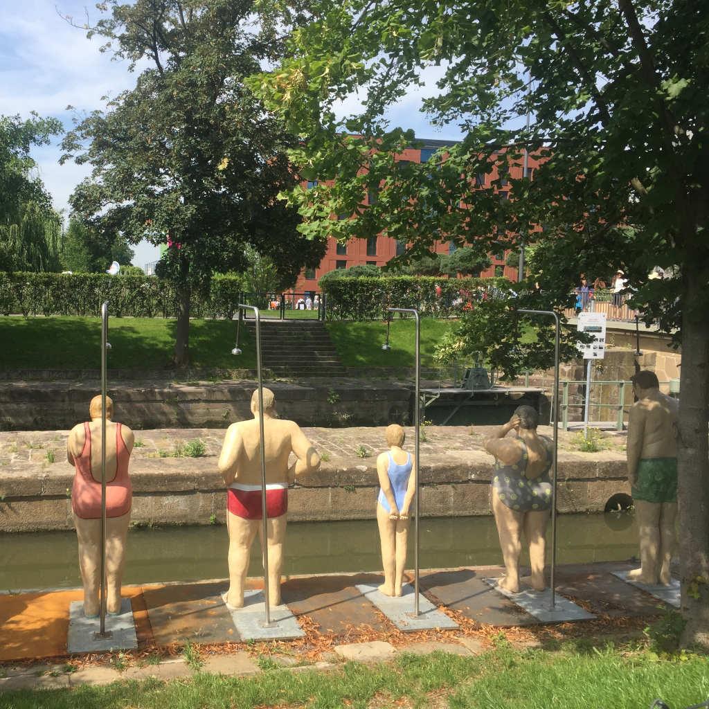 Besondere Gäste auf der BUGA Heilbronn: Fünf Skulpturen in Badekleidung - drei weiblich, zwei männlich – stehen mit dem Rücken zum Betrachter zum Wasser. Jeder von ihnen steht unter einer Dusche.