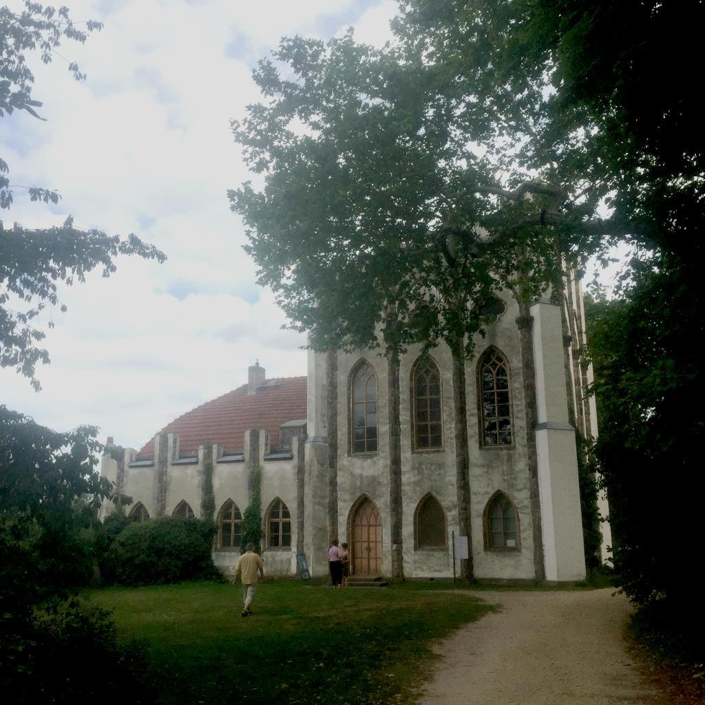 Ein weißgetünchtes Gebäude im Stil eines Karmeliter Klosters. Es ist gerahmt von Bäumen.