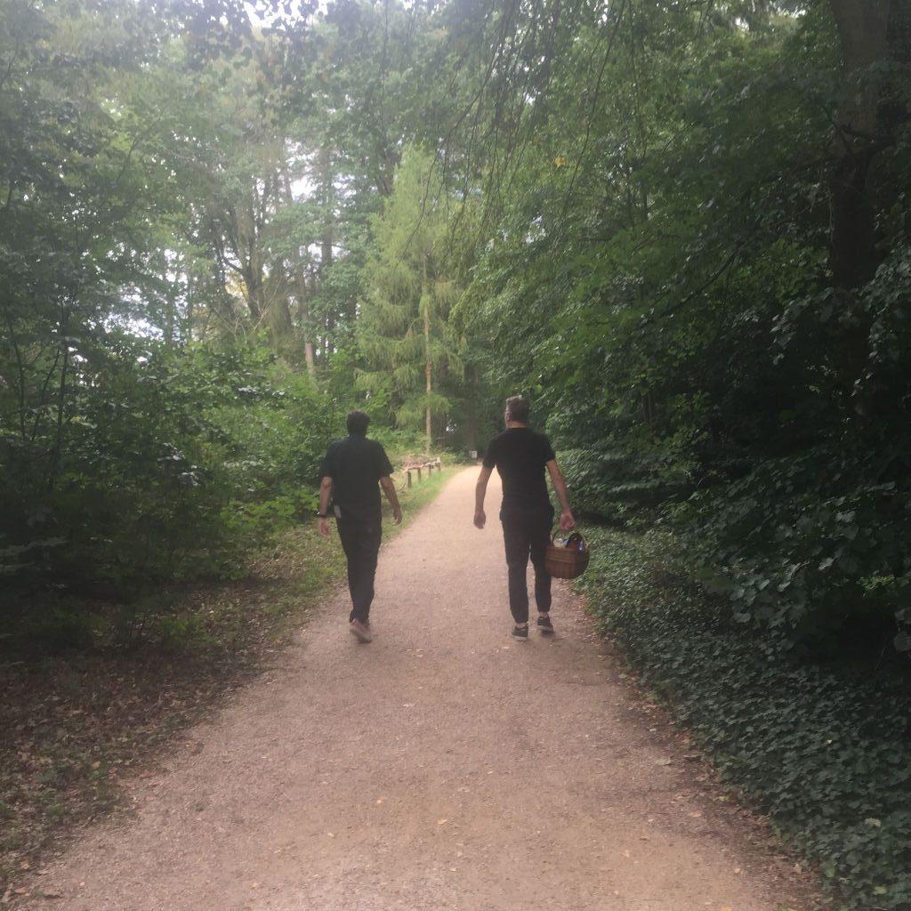 Zwei Männer von hinten gehen auf einem von Wald gesäumten Pfad. Der rechte trägt einen Picknickkorb.