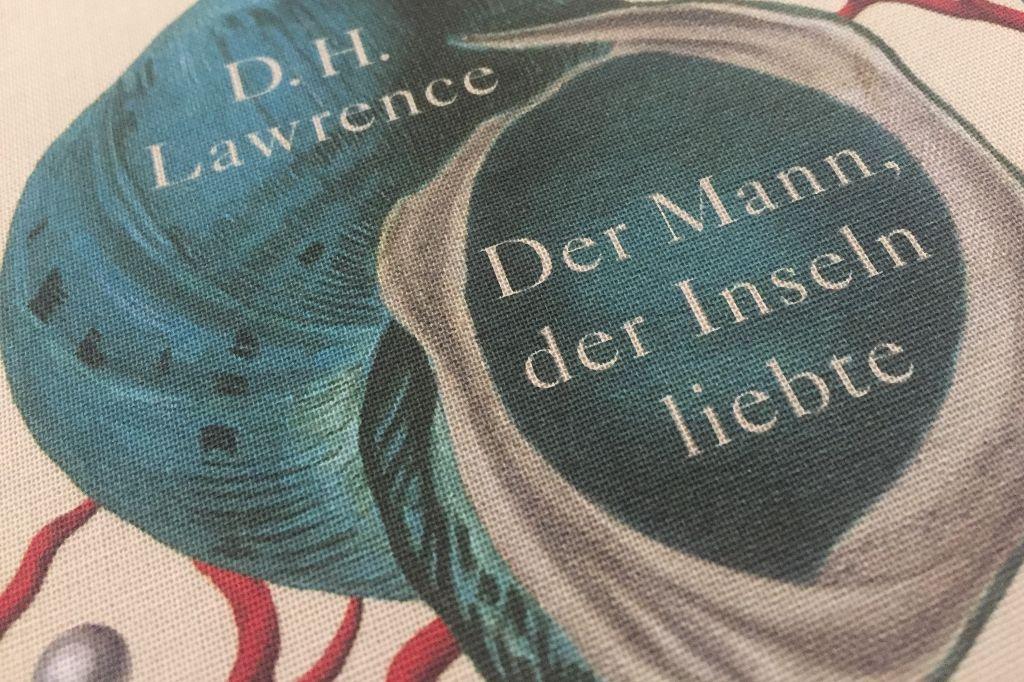 Das Bild zeigt ein Detail des textilbespannten Einbandes vom Buch Der Mann der Inseln liebte. Zu sehen ist er Autorenname, der Schriftzug des Titels sowie Muscheln und Perlen im Anschnitt.