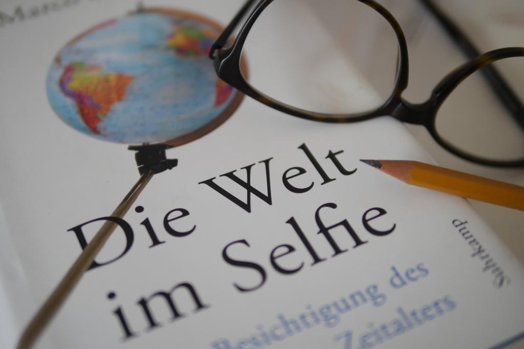 Buch mit dem Titel die Welt im Selfie. Auf dem Cover ist eine Weltkugel an einer Selfie-Stange zu sehen. Daneben liegt eine Brille und ein Bleistift.