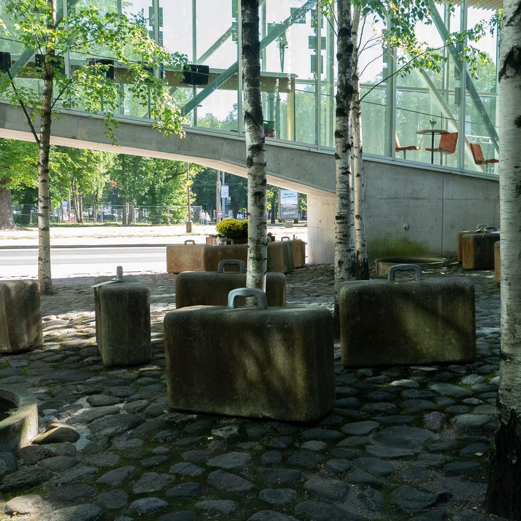Eingangsbereich in ein modernes Gebäude, in einem gepflasterten Innenhof wachsen Birken, zwischen die Bäume sind Koffer aus Beton abgestellt. Das Okkupationsmuseum ist bei einer Tallinn Reise ein bedeutenden Tallinn Tipp.