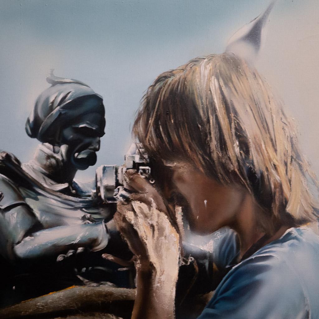Das Foto eine Gemäldes zeigt einen Fotografen mit blonden Haaren, der seine Kamera vor das Auge hält und sein Motiv fixiert.