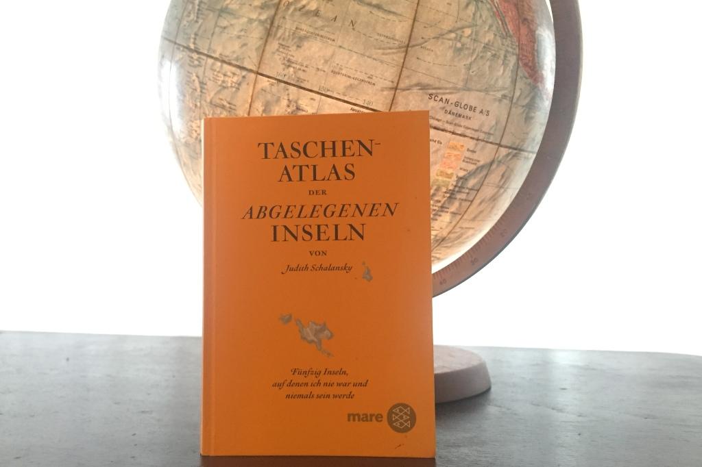 Das Bild zeigt das Buch Taschenatlas der Abgelegenen Inseln und einen Globus. Das Buch lehnt an dem Globus. Der Globus leuchtet von innen.