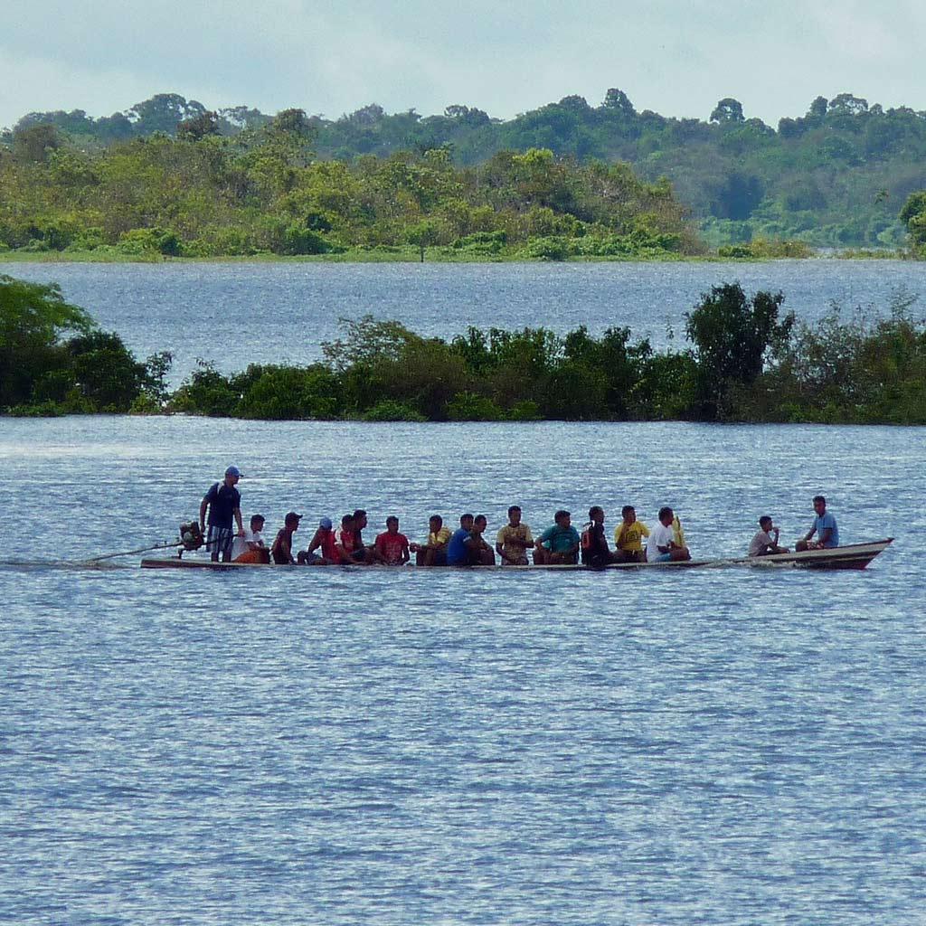 Ein vollbesetztes Langboot auf einem der Nebenflüsse des Amazonas
