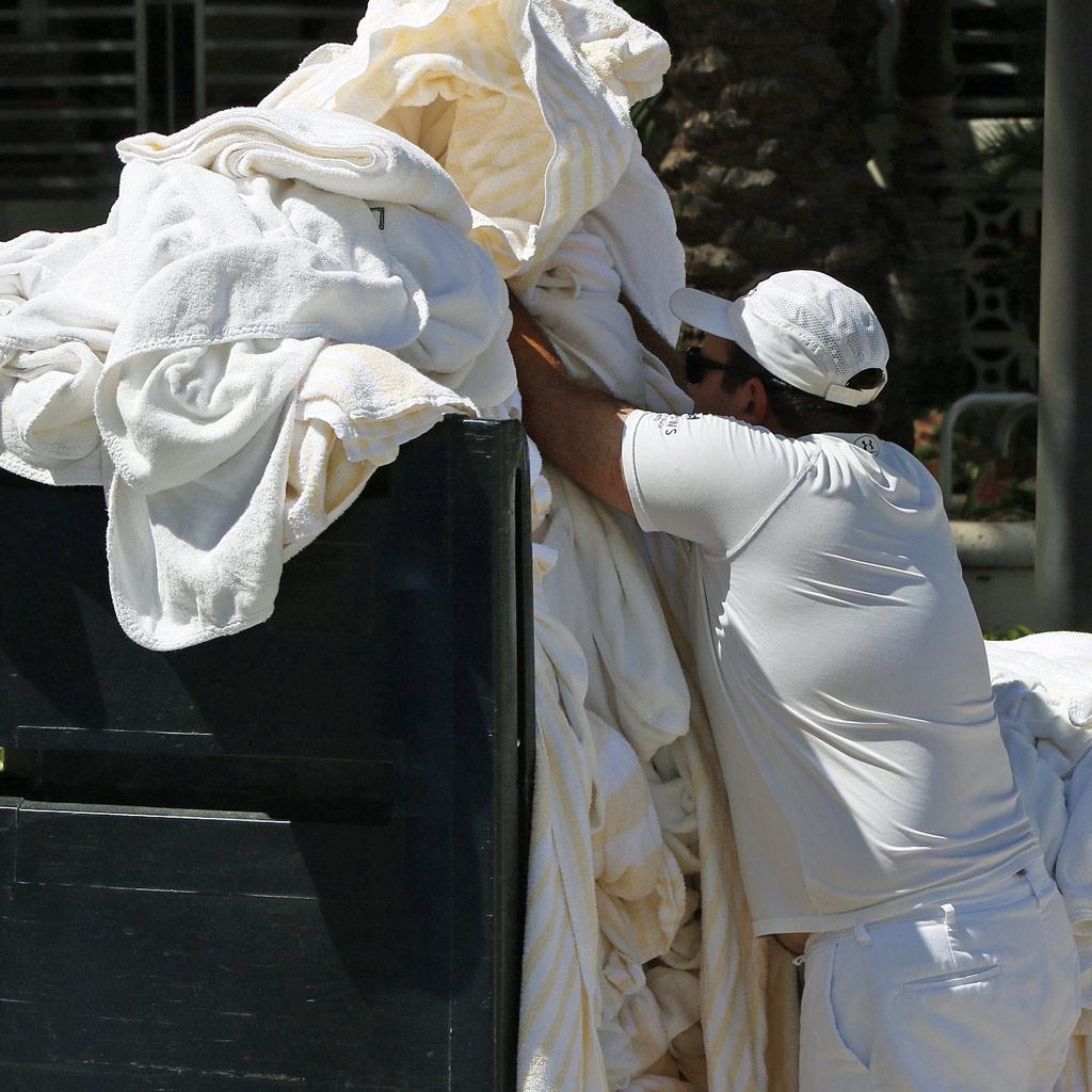 Ein Mitarbeiter einer Wäscherei sammelt benutzte Handtücher einer Hotels auf einem Rollwagen.