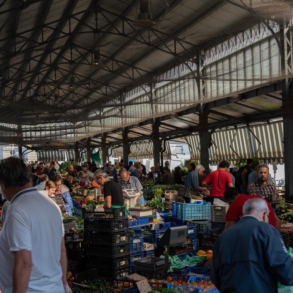 Ein Halle aus Glas und Stahl errichtet. In der Halle sind Gemüsekisten aufgestellt, Menschen suchen sich Gemüse aus diesen Kisten aus, dieser Markt ist ein super Turin Tipp.