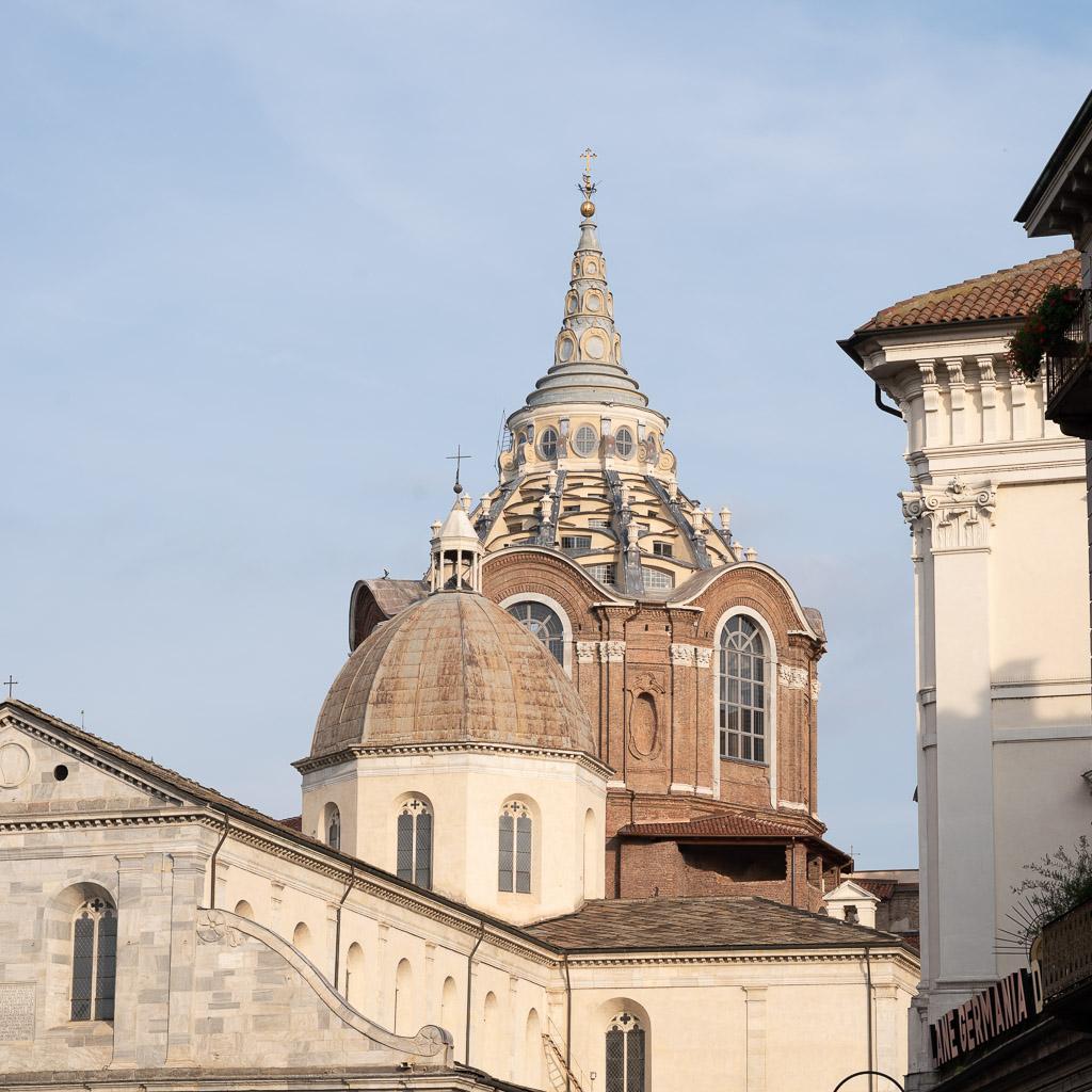 Eine Kirche von außen. Auf der Vierung der Kirche ein achteckige Kuppel, dahinter eine hochaufragende Kuppel mit einer spitzen Laterne.