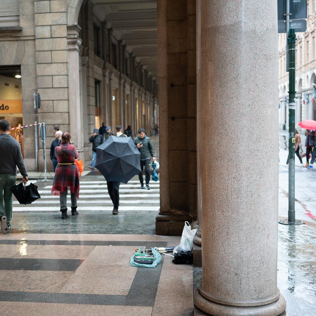 Rechts im Bild eine Säule aus Granit. Ein Mann mit einem Schirm, den er vor dem Körper hält, läuft uns entgegen.