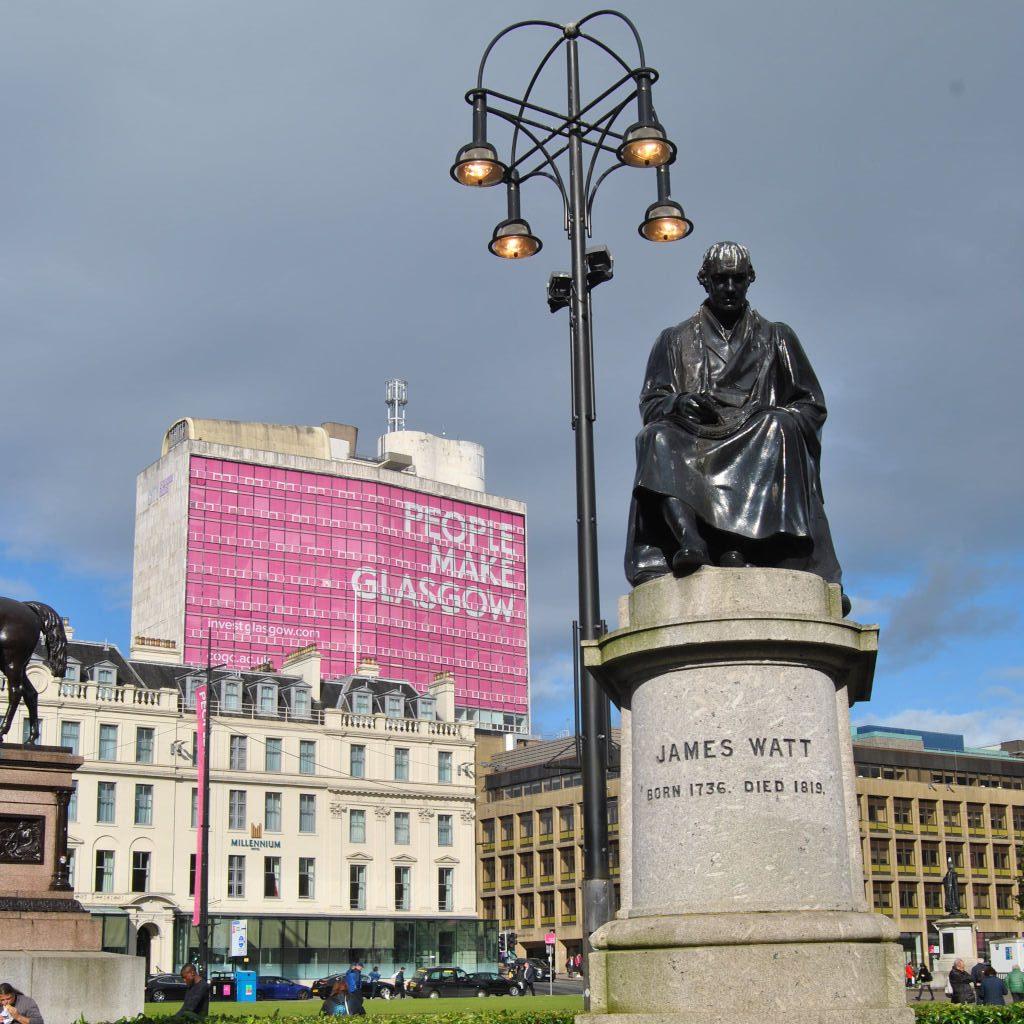 George Square in Glasgow. Eine Straßenlampe teilt den Bildgrund in zwei Hälften. Im linken Bildfeld neoklassizistische und brutalistische Gebäude, davor ein Bus und menschliches Treiben. Rechts der Lampe, mehr im Vordergrund, die Skulptur des schottischen Erfinders James Watt