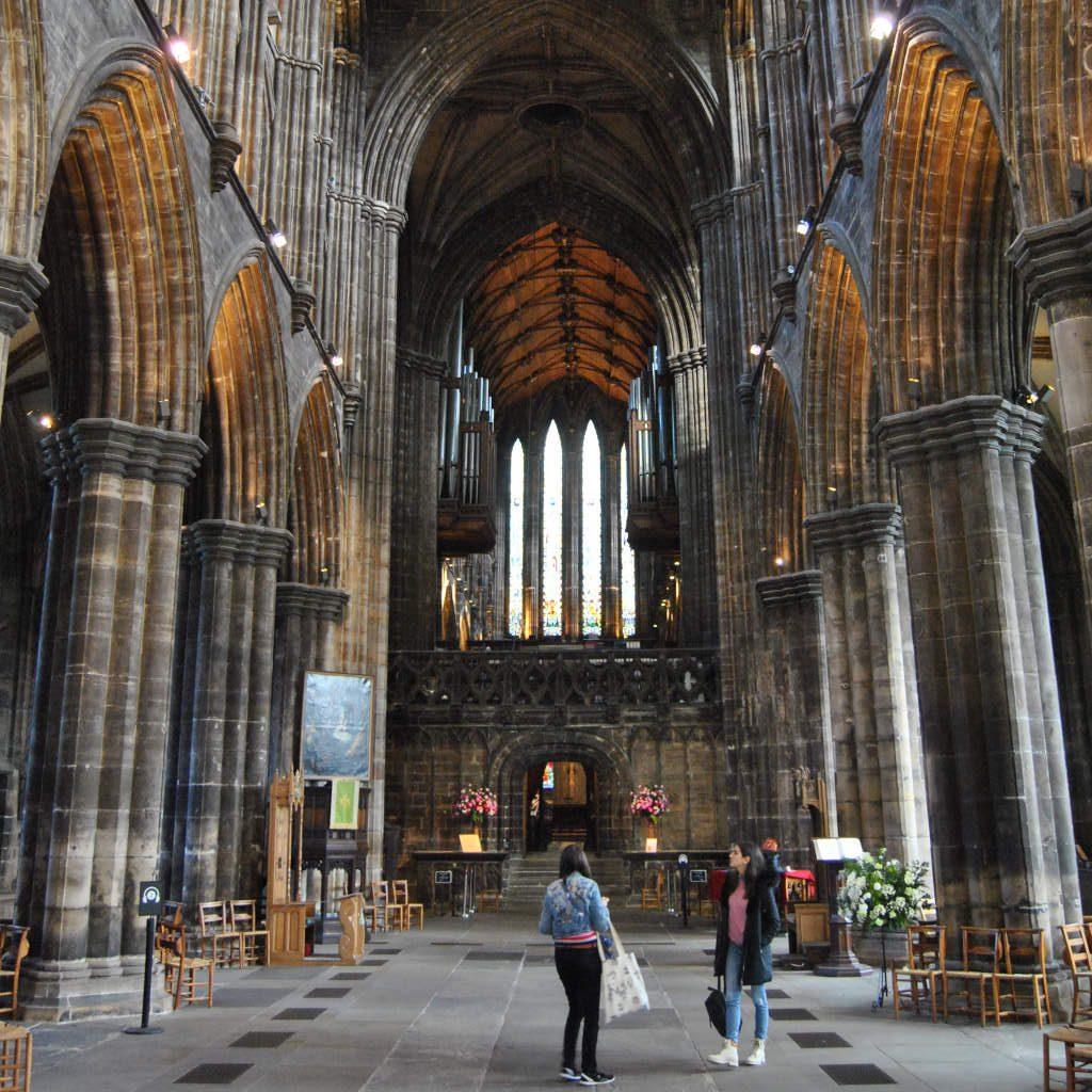 Innenraum einer Kathedrale, Blick in Richtung Hochaltar, im Vordergrund zwei Touristinnen.