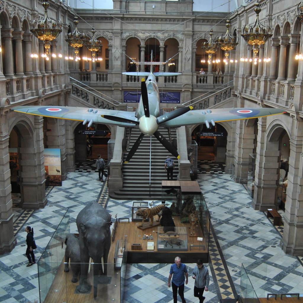 Blick von oben in den West Court des Kelvingrove Museums mit ausgestopftem Elefanten, Tiger und einem Flugzeug namens Spitfire.