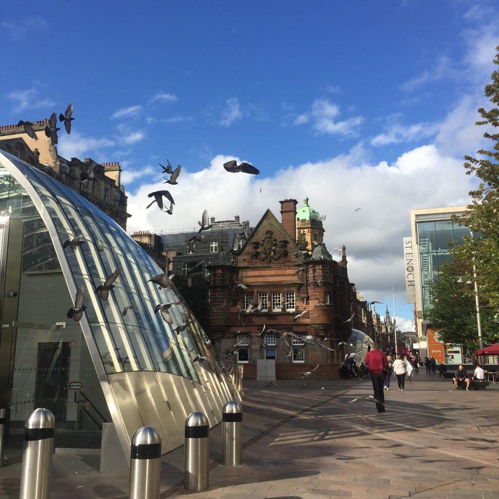 Im Vordergrunf ein Metro-Eingang in einer Einkaufsstraße in Glasgow. Ein Schwarm Vögel fliegt durchs Bild. Im rechten Bildhintergrund das Shopping Center St. Enoch.