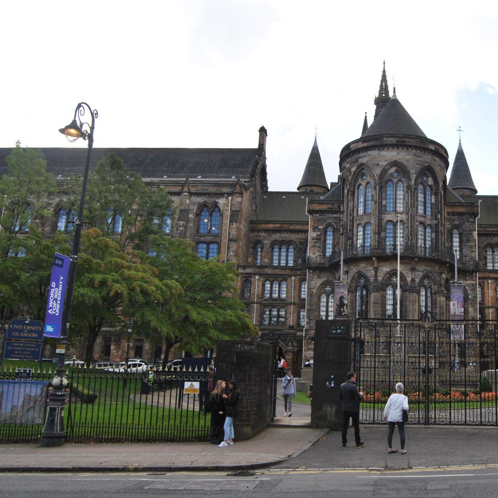 Blick auf den neogotischen Haupteingang der University of Glasgow. Vor dem Tor schauen einige Besucher auf die berühmte Alma Mater.