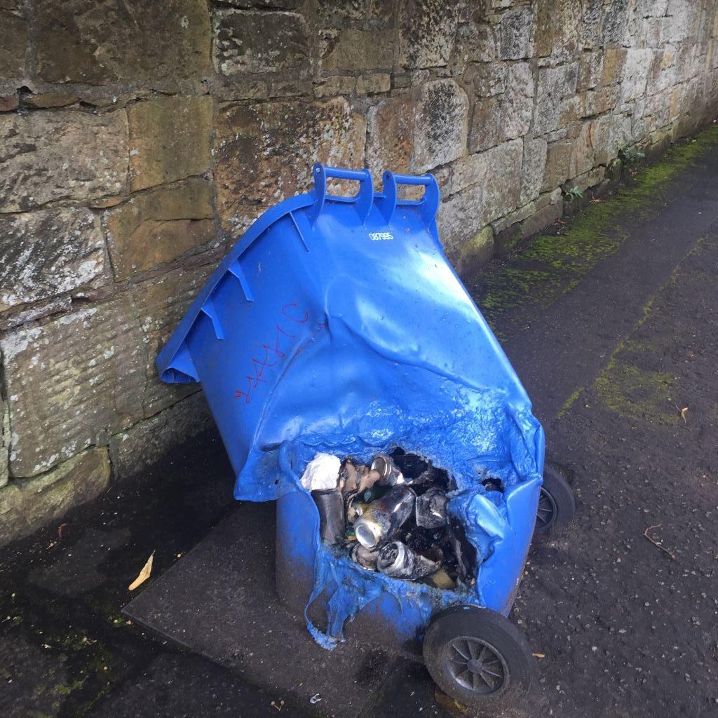 Eine blaue Mülltonne lehnt an einer grauen Steinwand. Durch eine von Feuer geschmolzene Öffnung sind leere Getränkedosen zu sehen.