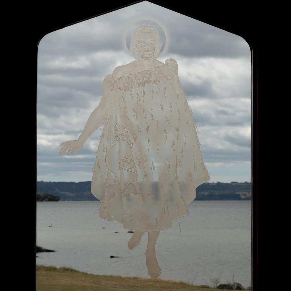 Blick aus einem Kirchenfenster auf den See von Rotorua. In das Glas ist ein in der Luft schwebender Mann dargestellt, dessen Fuß die Oberfläche des Sees gerade eben berührt.