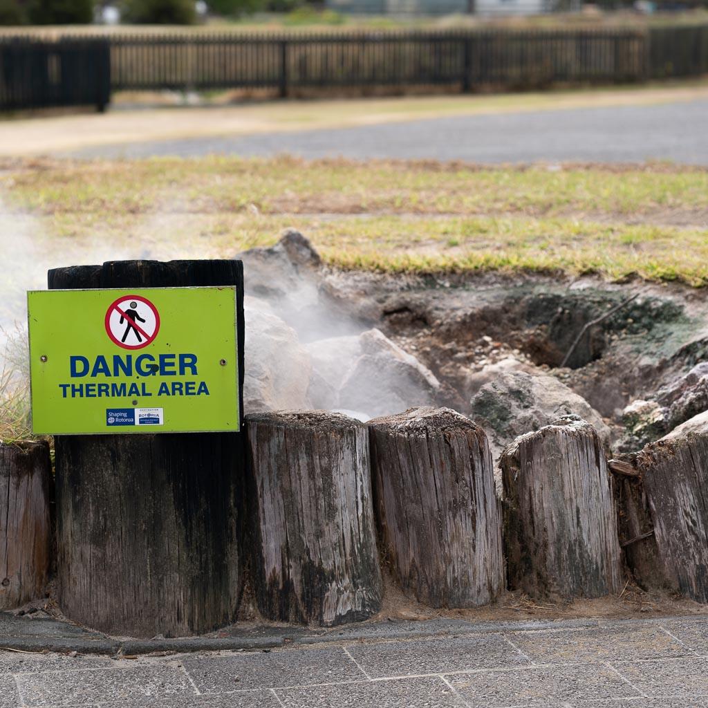 Eine Straßenkreuzung in Rotorua. Auf einem grasbewachsenen Streifen ist eine Schlammpfütze mit Holzpfählen gesichert. Im Vordergund steht ein Warnschild.