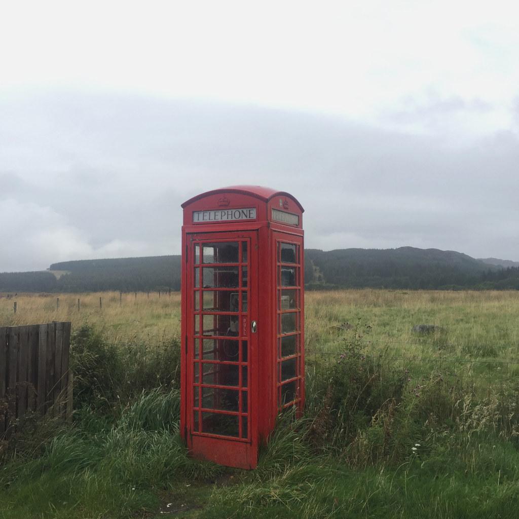 Eine alte britische Telefonzelle in dem klassischen Rot-Ton steht mitten in der Natur der schottischen Highlands.