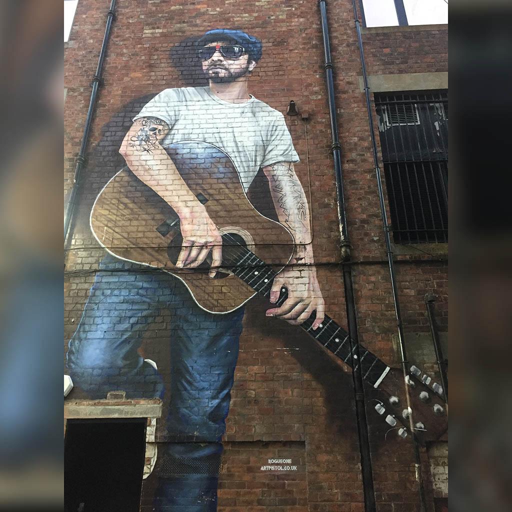 Ein überlebensgroßes Street Art Bild eines Gitarristen mit Sonnenbrille. Der Mann trägt ein weißes T-Shirt und eine blaue Jeans, der rechte Oberarm ist tätowiert..