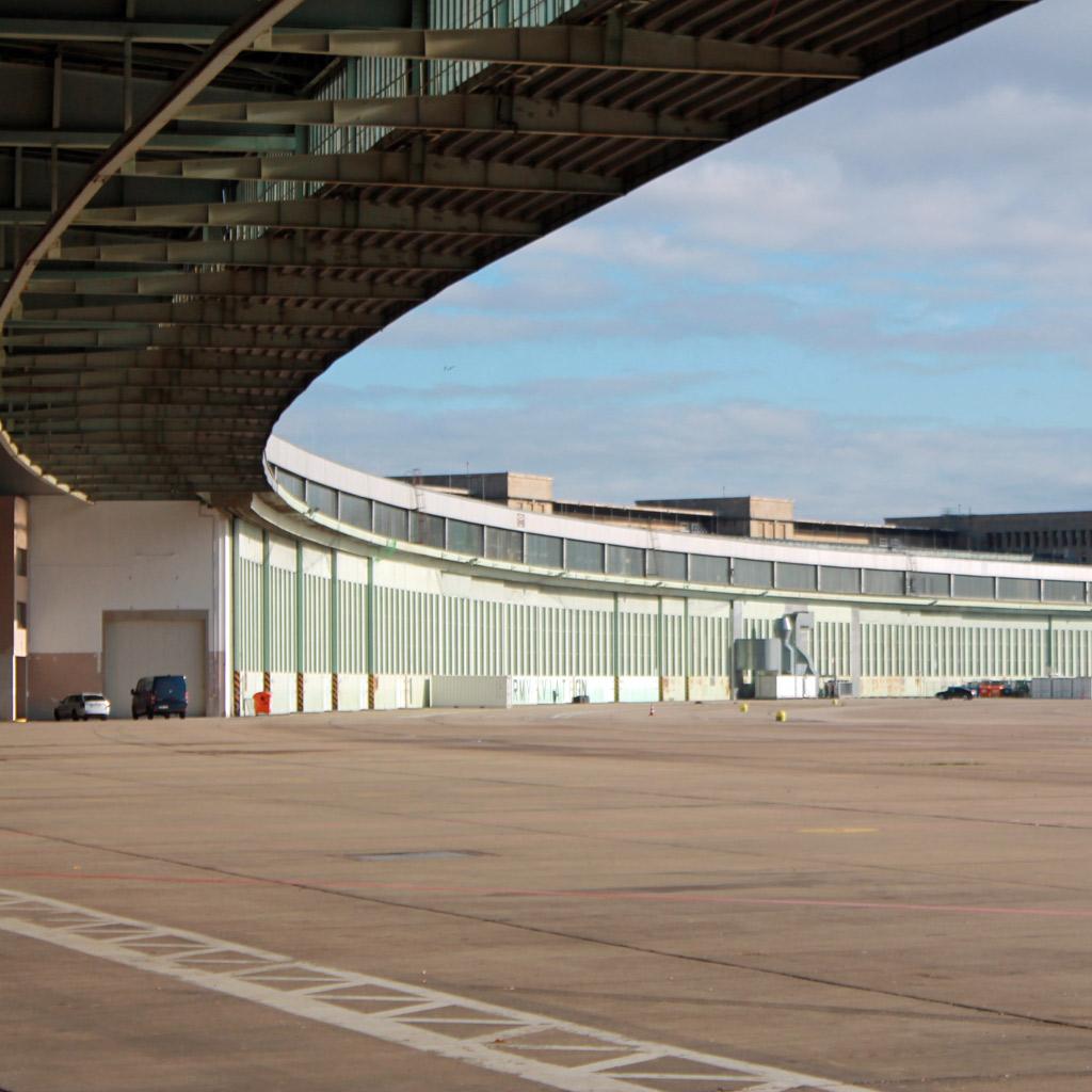 Ansicht der elegant geschwungenen, stützenlosen Stahlkonstruktion des Flugsteigs mit den direkt anschließenden Hangars im Hintergrund