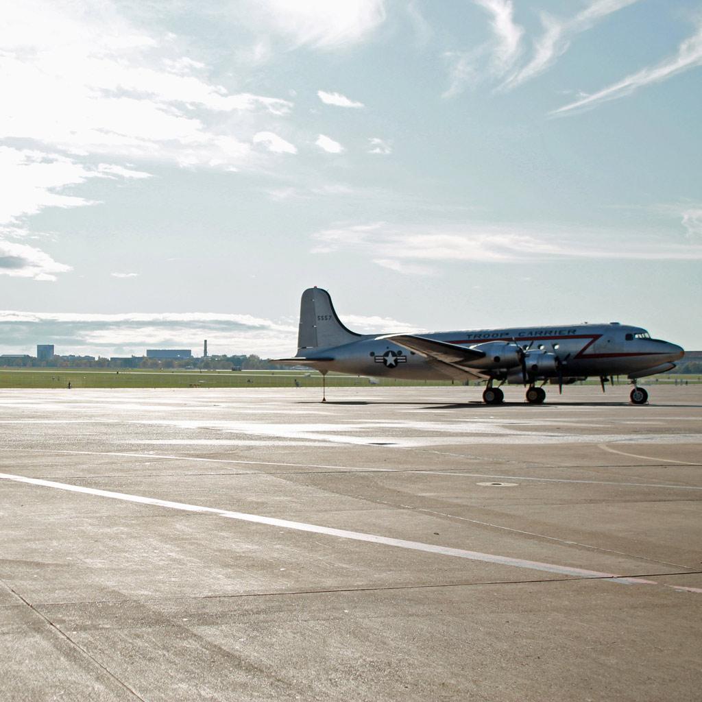 Blick über das Tempelhofer Flugfeld. Im Vordergrund steht ein historischer Truppentransporter mit der Flugzeugkokarde der United States Air Force