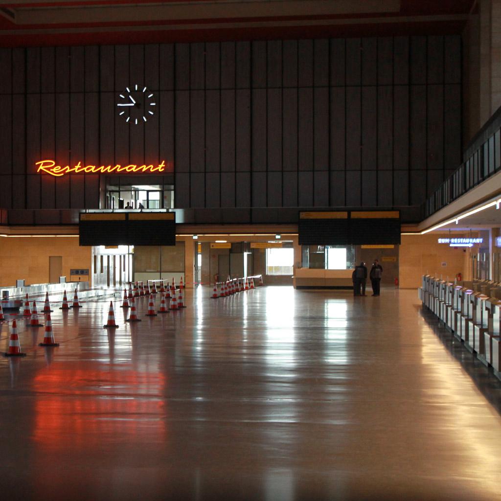 """Blick durch die hohe Abfertigungshalle mit dem Wort """"Restaurant"""" in oranger Leuchtschrift an der Rückwand"""