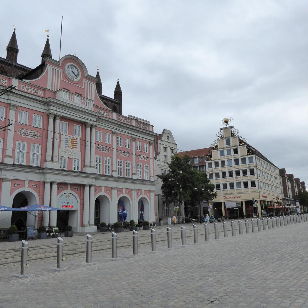 Blick auf die rosafarbene Fassade des Rathauses von Rostock.