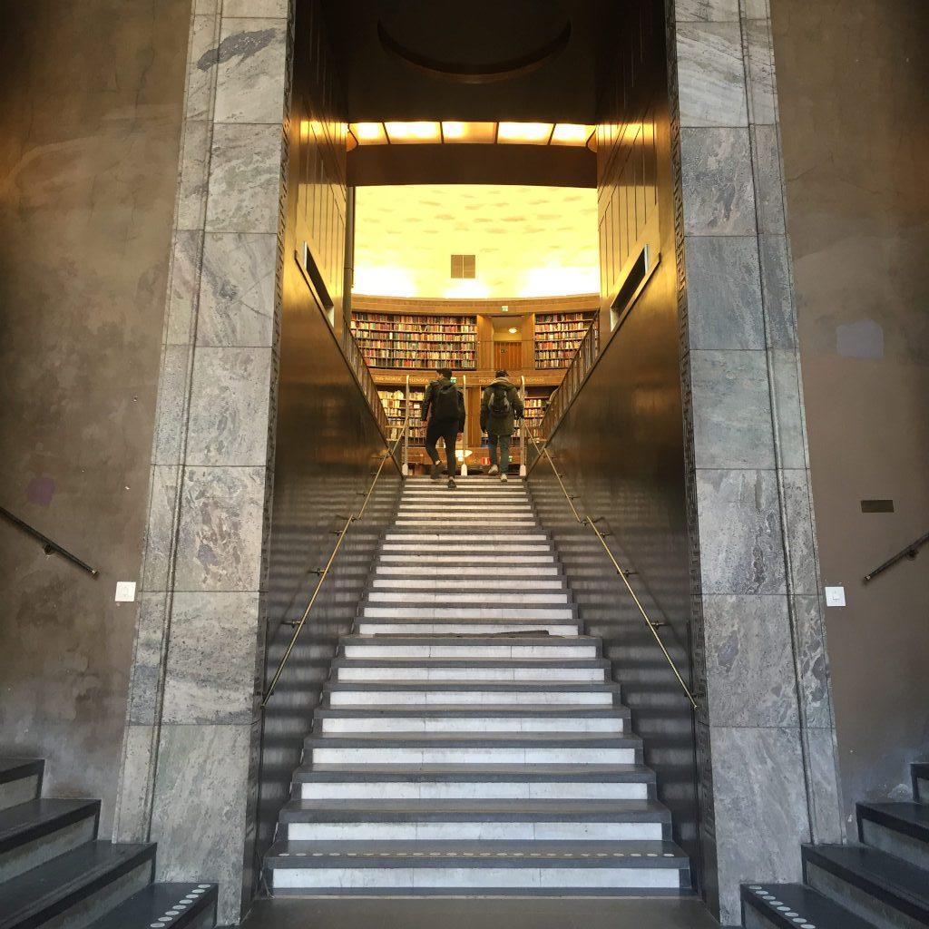 In der Bildmitte eine Treppe, gerahmt von Marmorsäulen. Am oberen Ende der Treppe sind zwei Personen zu erkennen. Sie betreten eine Bibliothek..