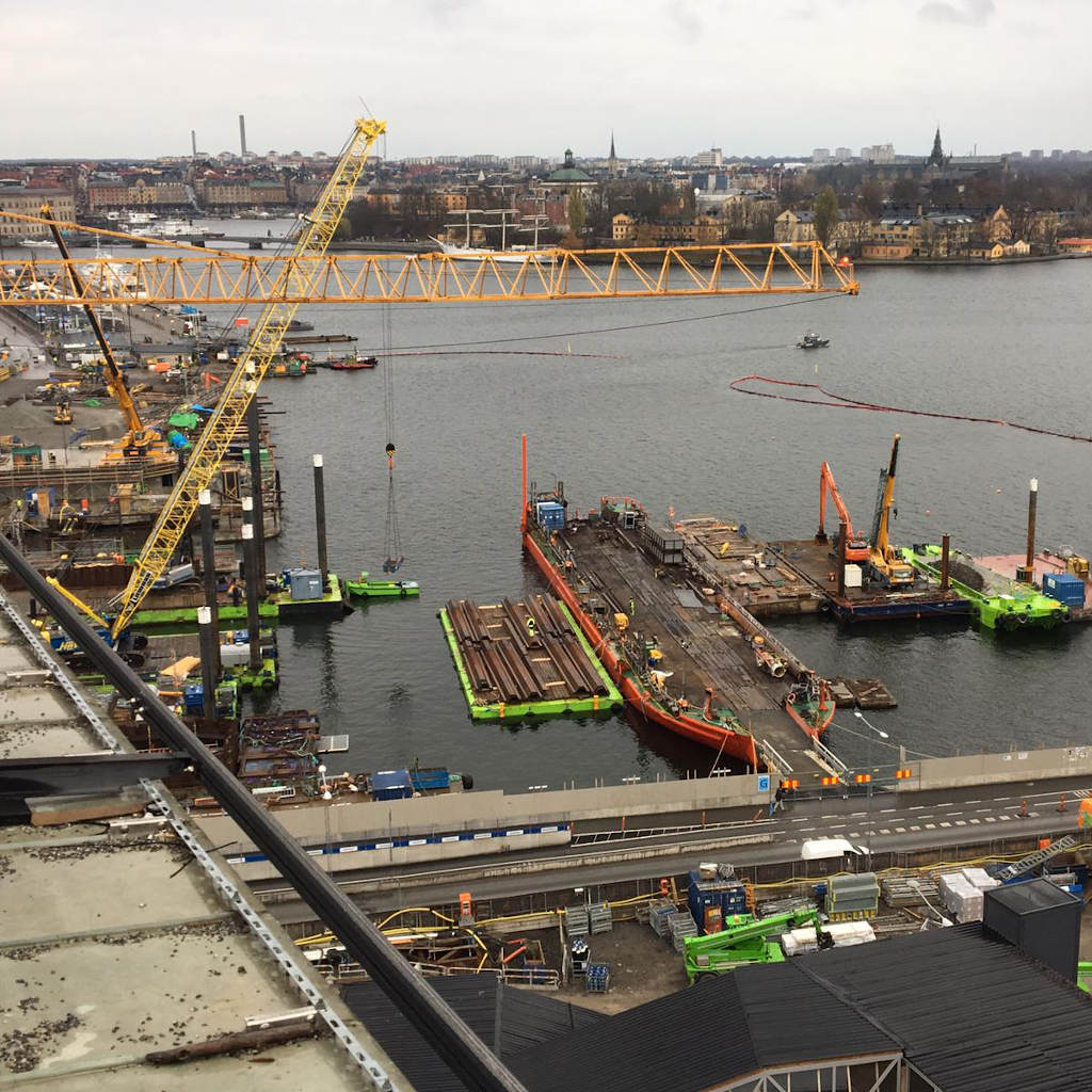 Blick auf eine Baustelle am Wasser von oben. Links ragen Kräne ins Bild, weitere Baustellenbereiche auf Pontons scheinen über dem Wasser zu schweben.
