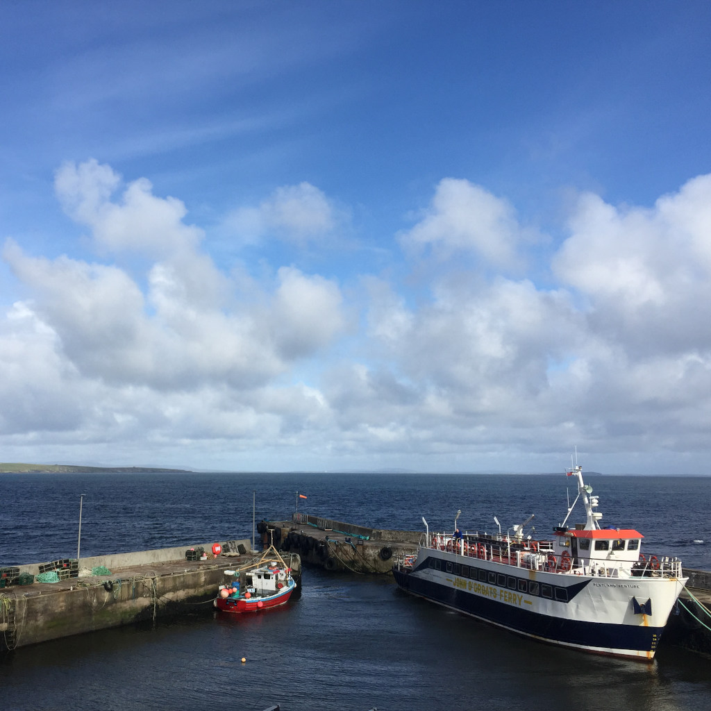 An einer engen Hafeneinfahrt liegen zwei Schiffe. Ein Fischerboot und eins Passagierfähre.