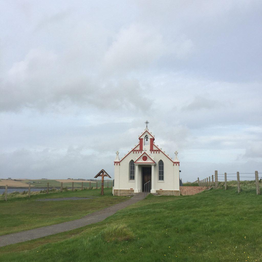 Eine kleine Kapelle liegt inmitten grüner Küstenlandschaft.