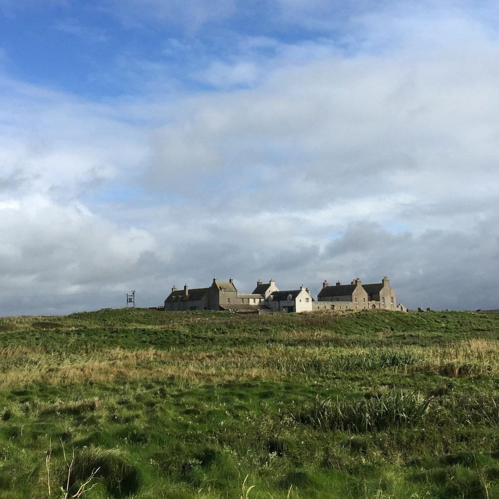 Ein steinernes Herrenhaus liegt auf einem Hügel in einer weiten schottischen Landschaft mit tief hängendem Himmel.