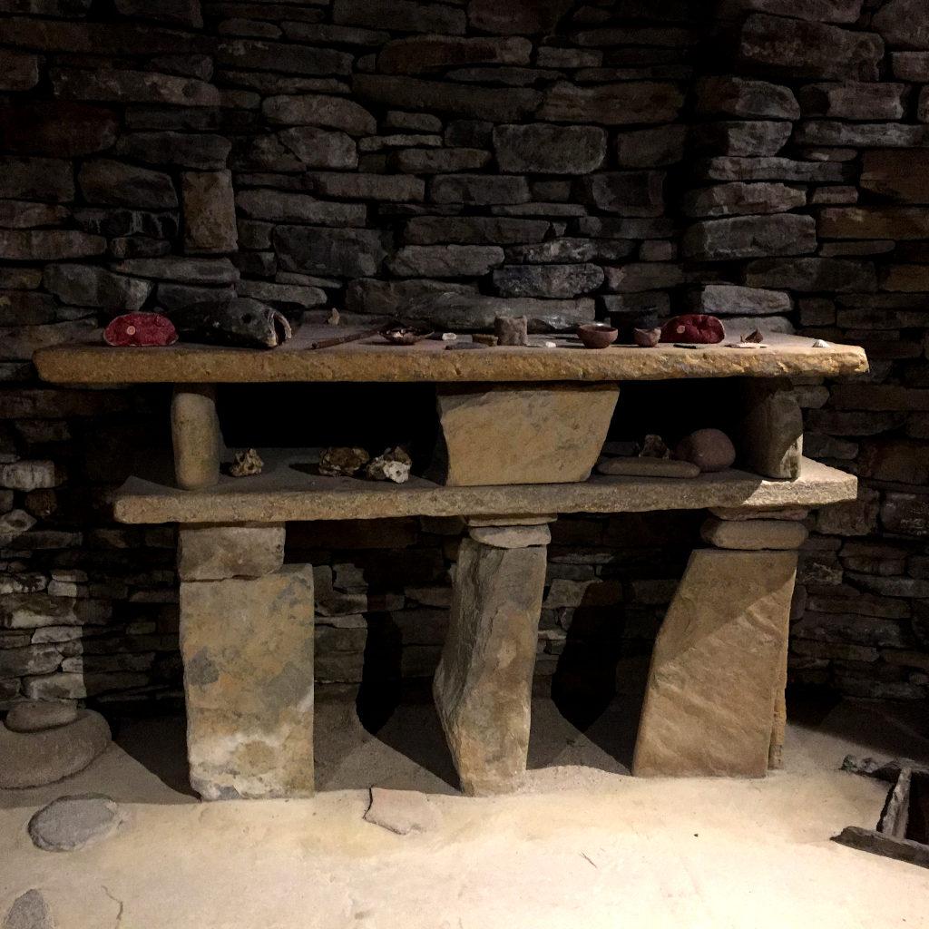 Ein offenes Steinregal vor einer Steinwand. Ein jungsteinzeitliches Wohnhaus. Auf dem Regal liegen Gegenstände wie Schinken und Werkzeuge.