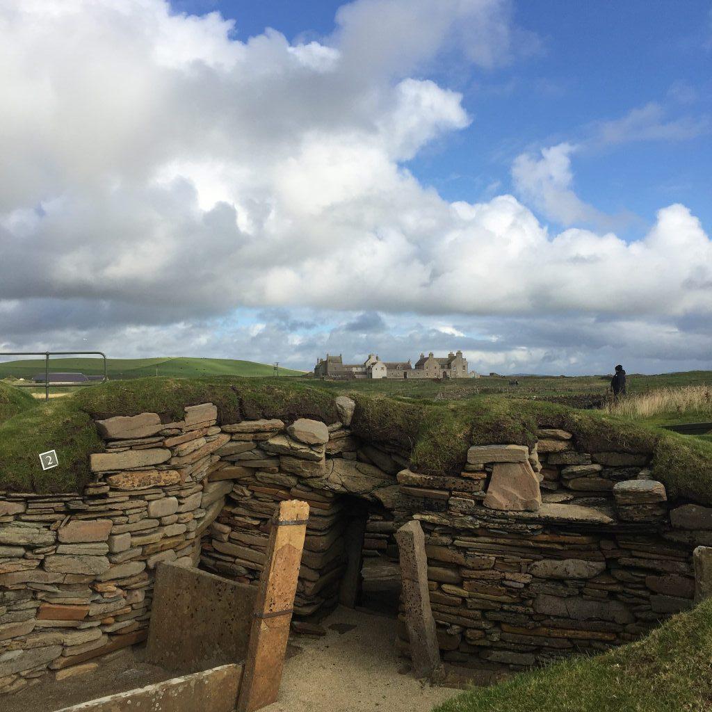 Ein archäologisches Setting in Skara Brae. Beschriftete Ausgrabungen vor wolkigem weitem Himmel.