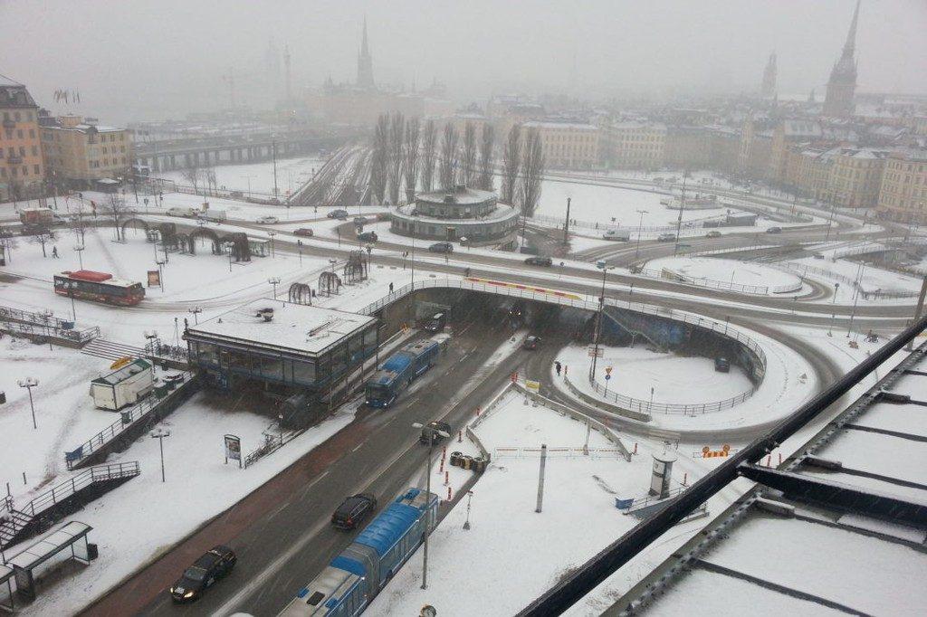 Eine Baustelle im Schnee. Die Gebäude im Hintergrund verschwinden in diesiger Luft.