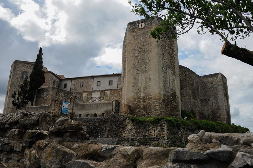 Das Kastell von Melfi ist ein großer viereckiger Baukörper von Türmen flankiert, der auf einem Felsen steht.