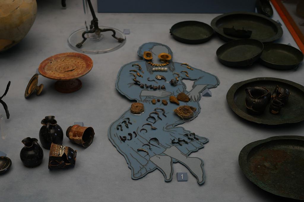 Vitrine im Museum von Melfi mit Grabbeilagen eines Frauengrabs. Der Umrisse einer Frau ist mit Schmuck ausgefüllt.