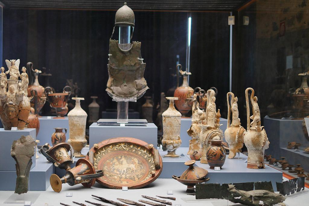 Vitrine im archäologischen Nationalmuseum von Melfi. Im Zentrum die bronzene Rüstung eines Soldaten.