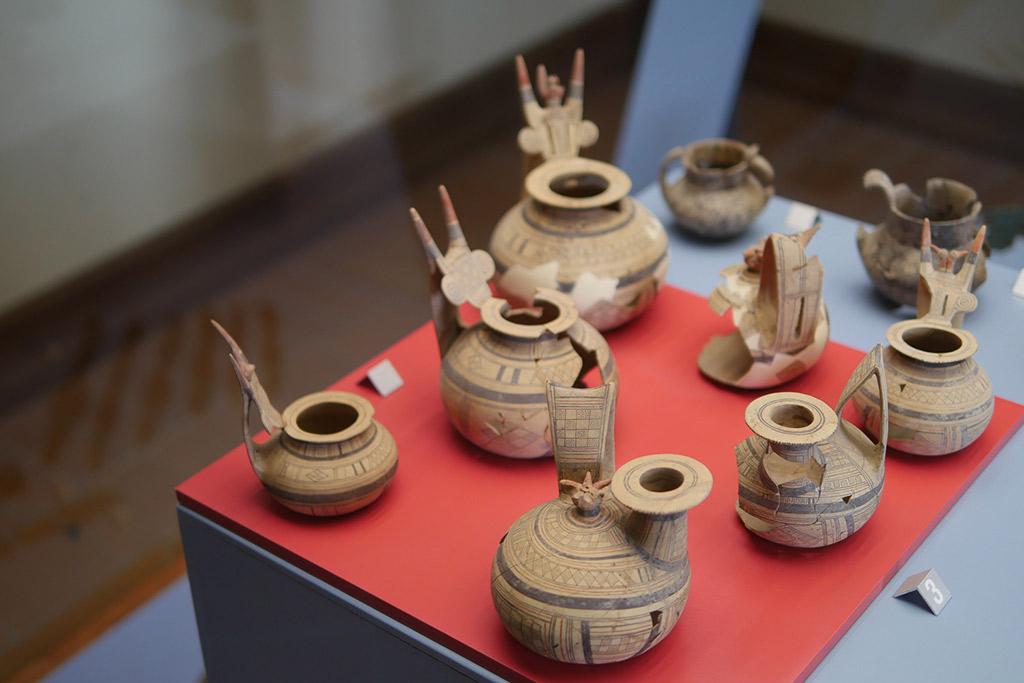 Kleine Tongefäße mit geometrischen Mustern und Stierköpfen in einer Vitrine im Museum von Melfi ausgestellt.