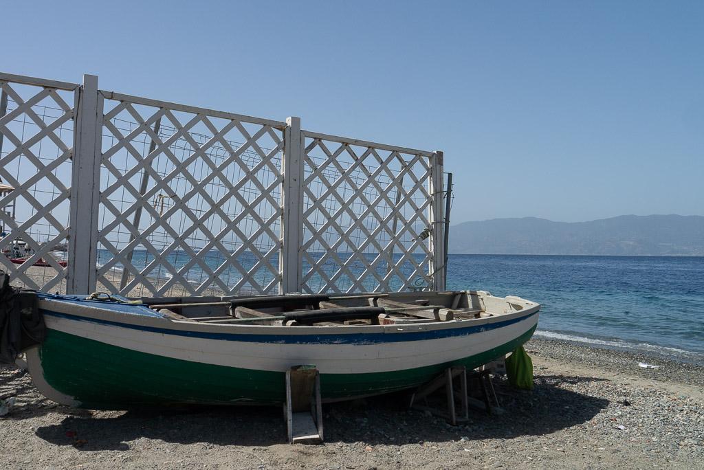 Der Strand von Reggio Calabria. Im Vordergrund ein Ruderboot und im Hintergrund die blauen Berge von Sizilien.