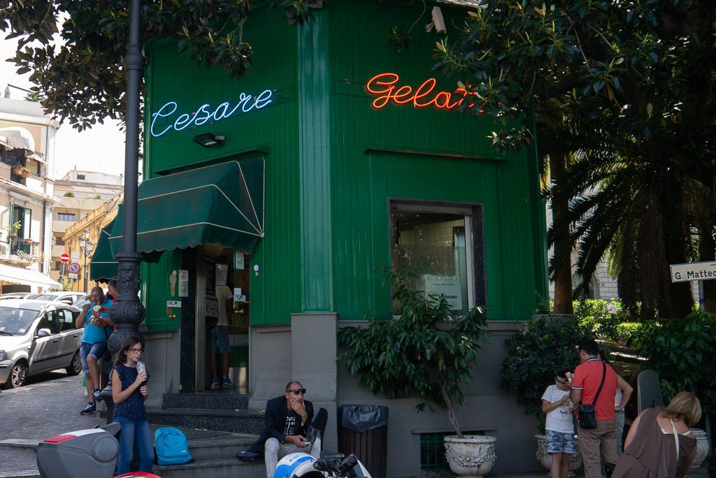 """Ein grüner Pavillon im Zentrum von Reggio Calabria. In Leuchtschrift ist """"Cesare Gelato"""" geschrieben. Vor der Eisdiele stehen und sitzen Menschen, die Eis essen."""