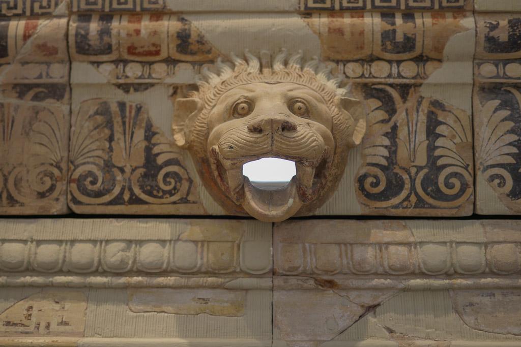 Fries eines griechischen Tempel aus Ton, bemalt mit den Farben Rot und Blau. Im Zentrum ein maskenhafter Löwenkopf.