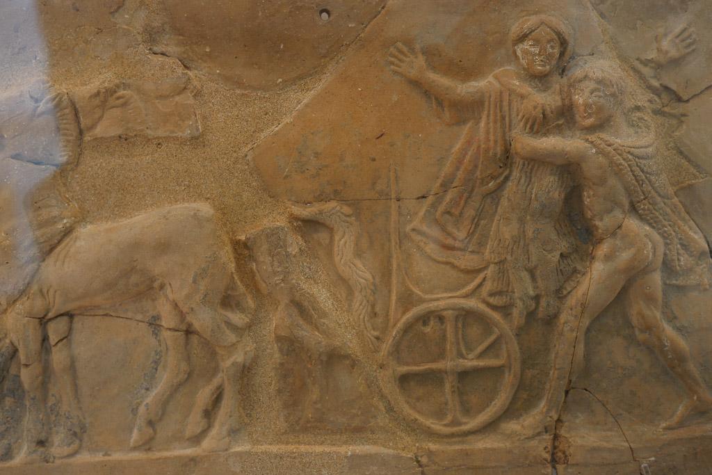 Tonrelief aus dem Nationalmuseum Reggio Calabria mit einen Mann, der eine Frau auf einen Wagen hebt.