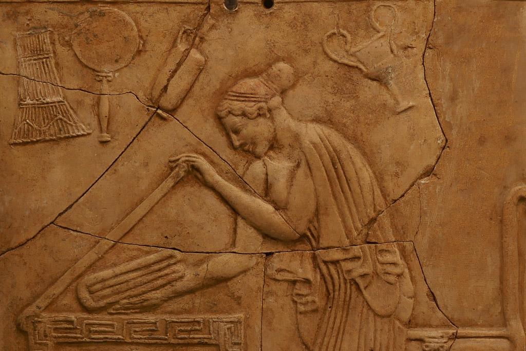 Die Tontafel im Archäologischen Museum Reggio Calabria zeigt eine Frau, die in eine Truhe ein gefaltetes Tuch legt.
