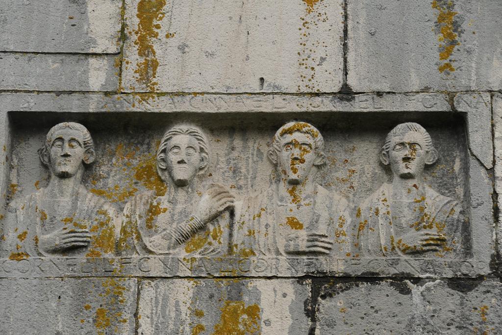 Römisches Relief mit Oberkörpern von vier Männern inToga in eine Mauer eingemauert.